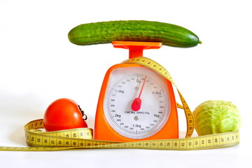 yellow measuring tape and thekitchen  scales, diet vegetables, cabbage, cucumber, tomatoes, isolated on white background