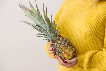 Closeup of a juicy pineapple in hands of woman on yellow sweater background. Healthy food.