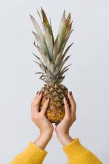 Closeup of fresh pineapple in woman's hands on light blue background.