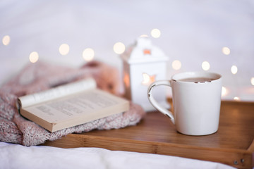 Mug of coffee with opn book and knitted sweater on wooden tray close up over Christmas lights. Good morning. Holiday season.
