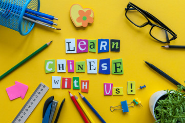 Word LEARN CHINESE WITH US made with carved letters on yellow desk with office or school supplies, stationery. Concept of chinese language courses