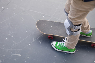 Top view on child's feet in green sneakers standing on skate. Active boy skating outdoors.