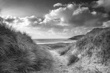 Beautiful black and white  landscape image of Freshwater West beach with sand dunes on...