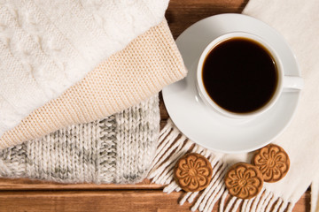 Stack of cozy knitted warm sweater , wooden background . Sweaters in retro Style and a Cup of coffee. The concept of warmth and comfort.