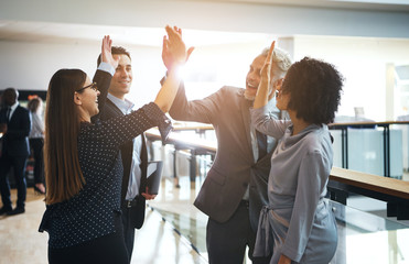 Smiling business colleagues high fiving each other in an office