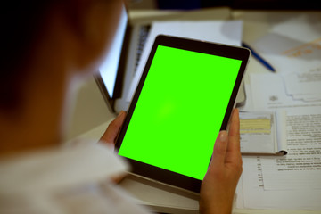 Rear view of blurred woman holding a tablet with a blank editable green screen.