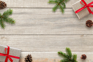 Christmas wooden background with fir branches, pinecones and gifts. Top view with copy space for text.