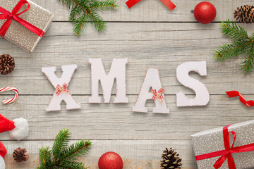 Xmas white letters on wooden table surrounded with Christmas decorations, gifts, fir branches, balls, Santa hat and pinecones. Top view.
