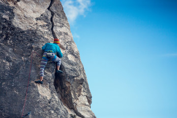 Poster de jardin Alpinisme The girl climbs the rock.