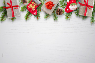 Christmas background with gifts, socks, pinecones and fir branches on top. Clean white wooden table with space for text. Top view.