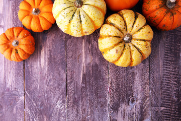 Many orange pumpkins on wooden background, Halloween concept.