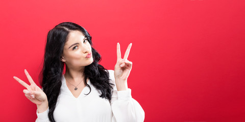 Young woman giving the peace sign on a solid background