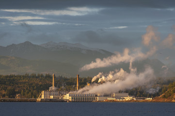 Industrial Pulp Mill in Port Townsend, Washington. The Olympic Mountains provide a backdrop to the historic pulp mill located along the waterfront of the maritime city of Port Townsend.