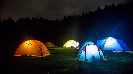 Lighting camp tents with forest in background