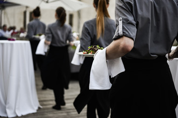 Waiters carrying plates with meat dish on some festive event