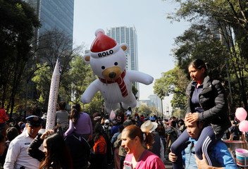 """A balloon in the shape of a bear character named """"Bolo"""" floats during a Christmas parade along Reforma avenue, in Mexico City"""