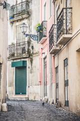 Budynki na wąskiej brukowanej uliczce w Lizbonie z metaloplastyką - 182215766