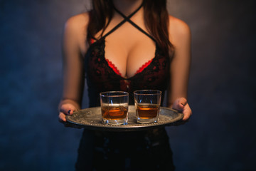 Sexy woman holding a tray of alcohol drinks. Bad habits. Immoral lifestyle. Elite night clubs for rich people concept