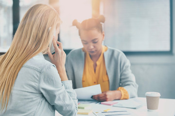 Two female students prepare project together. Back view of blonde woman speaks over modern smart phone as manages finances while her partner studies documents. Cooperation and team work concept