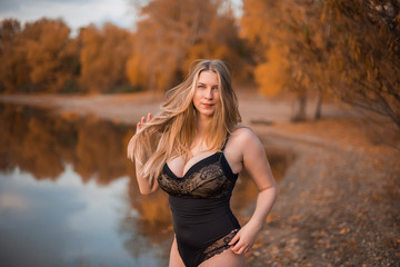 Young, sexy, chubby Girl in black lace body with very large Breasts lying in the yellow grass in the forest. Autumn, overcast.