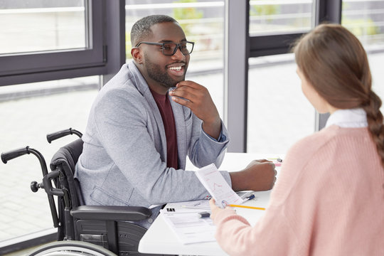 Portrait of glad positive male invalid in wheelchair looks with happy expression, glad to recieve high net profit. Business male coach checks projects of young female trainee, rejoice good results