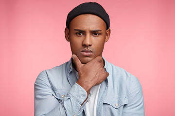 Isolated shot of mixed race dark skinned male has very serious and confident look, keeps hand under chin, wears trendy clothes, thinks about something important or makes decision, poses indoor