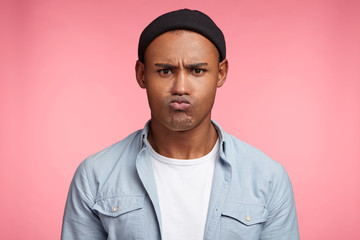 Grumpy dissatisfied mixed race male pouts lips, being angry with someone or offended, has unhappy expression, expresses his discontent. Black stylish male in fashionable clothes looks unhappy