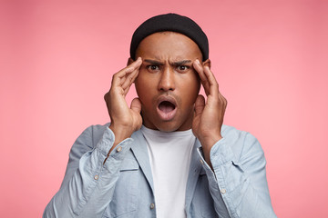 Horrified stunned mixed race male openes mouth widely, can`t undertand what happend, has puzzled expression, looks scaring, isolated over pink studio background. Amazed multiethnic fashionable man