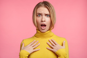 Shocked scared beautiful young woman keeps hands on chest, mouth widely opened, stares at camera realizes that she forgot to pay bills, recieves big fine, isolated over pink studio background.