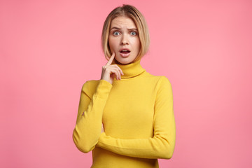 Waist up portrait of beautiful shocked young woman has light hair, wears yellow turtleneck sweater, looks with puzzled expression as hears something unexcpected, has problems or troubles in life