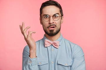 Portrait of dissatisdfied man wears round spectacles, has discontet, indigant look, gestures hand, being surprised with something, poses against pink studio background. Facial expression concept