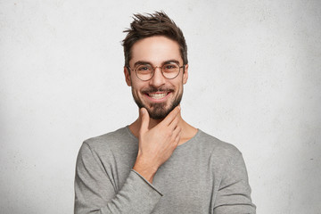 Smiling male worker has trendy hairdo, keeps hand under chin, wears casual clothes and optical glasses, looks directly into camera with happy confident expression, glad to be praised by boss