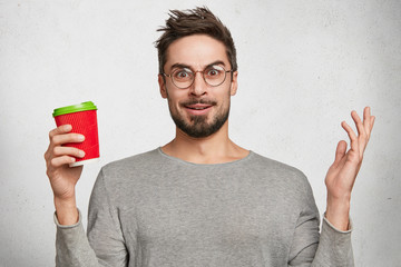 Bearded hipster male holds paper cup of coffee, gestures in bewilderment, has puzzled expression, wears rounded glasses, isolated over white background. Stylish student with takeaway cappucino