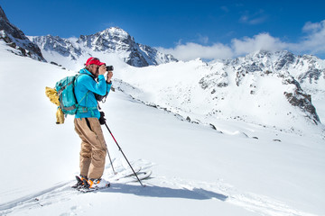A skier walks in the mountains