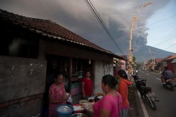 Villagers shop for food as Mount Agung erupts in the background in Culik Village, Karangasem, Bali