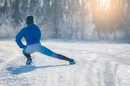 Runner stretching in winter Park. A healthy way of life.