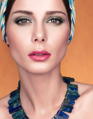 Beauty closeup portrait of beautiful young woman with kerchief on her head. Necklace on her neck