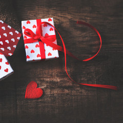 Valentine's Day card with red hearts, gift box with red ribbon and place for text. Valentines Day concept Background for design.