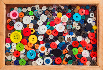 Plastic colorful buttons in wood container with border