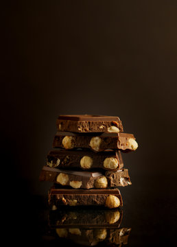 Slabs of dark chocolate with hazelnuts stacked on deep brown background