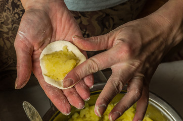 The hands of a woman cook cooked on a table of flour dough and make vareniki