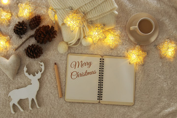 Notebook with text: MERRY CHRISTMAS and cup of cappuccino over cozy and warm fur carpet. Top view.