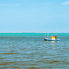 Small Blue Yellow wooden fishing boat in the sea