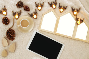 Houses shape wooden photo frames nect to tablet device with empty screen over cozy and warm fur carpet. Top view