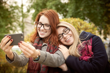 two young student girlfriend with long hair and glasses walking in the autumn Park dressed in a coat taking a selfie on the background of autumn Park in natural light