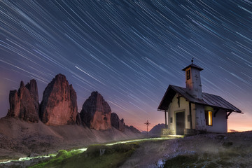 cool chapel in front of the tre cime di lavaredo in the dolomites south tyrol. Fading comet style startrails in the sky Fototapete