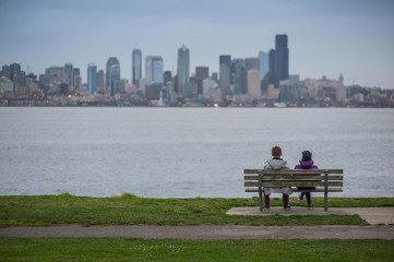 couple of people on the bench looking at the city