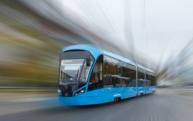 Blue electric tram on blurred background.