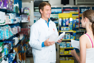 Man pharmacist helping customers