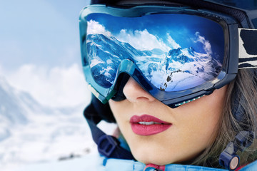 Poster Winter sports Portrait of young woman at the ski resort on the background of mountains and blue sky.A mountain range reflected in the ski mask